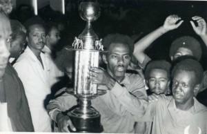 """Ali Gagarin con la Coppa d'Africa tra le mani. Presenti in foto anche Jaxa, altra stella del Sudan 1970 (dietro Gagarin), e Shawaaten, uno dei più forti difensori sudanesi di tutti i tempi soprannominato """"il Diavolo"""", sulla destra."""